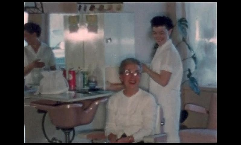 1950s: UNITED STATES: lady looks at self in mirror after hair cut. Toddler in beauty salon. Ladies at beauty salon.
