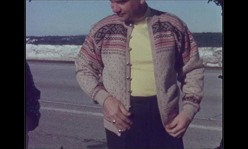 1960s: Woman walks past car, smiles. Man puts on sweater.