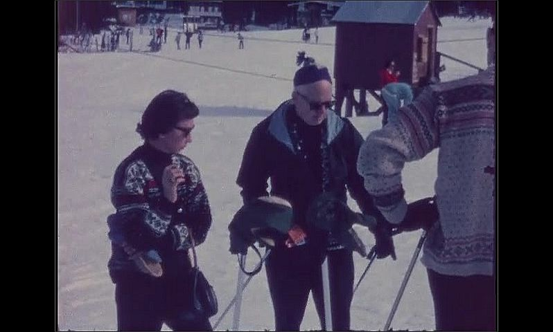 1960s: Woman stands at bottom of ski slope, smokes cigarette, talks. Men and women stand in group, talk.
