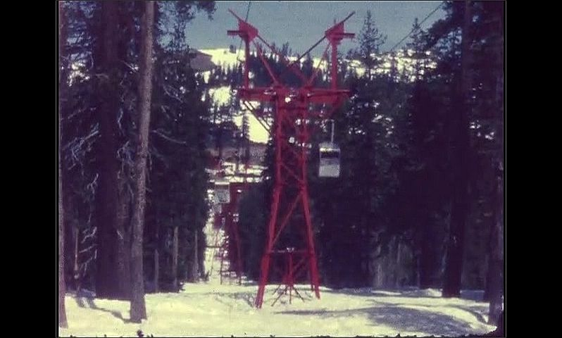 1960s: Snowy mountain. Ski lift. Man stands by wall, looks at skis.
