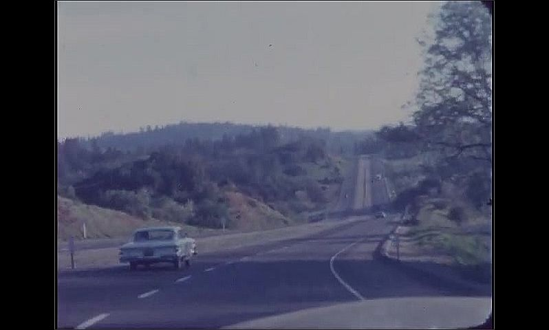 1960s: Woman waves, walks to car, gets in passenger seat. Car drives down highway. Billboard on side of the road.