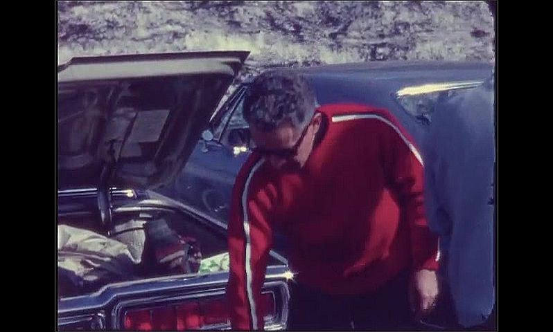 1960s: Man takes ski boots out of trunk, releases boots from holder.