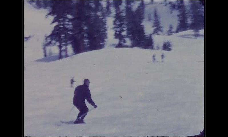 1960s: Man pushes off, skis down mountain, falls.