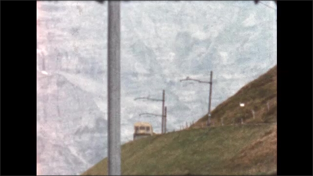 1950s: train driving around a mountain side, sign for Grindelwald in front of a building and a large mountain