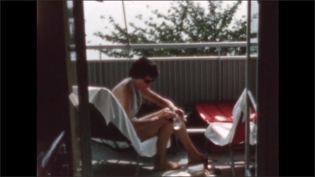 1950s: woman sitting on a chair on a balcony pouring herself a drink and then drinking from another glass