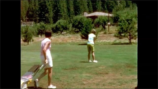 1960s: Golf course. Man and woman stand by two golf bags in distance. Ball bounces down the green. Woman lines up shot as other woman drags golf bag behind. Woman putts ball onto green next to man.