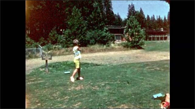 1960s: Golf course. Slow-motion of woman in green shorts hitting a ball down the course, watching it, picking up tee and walking.