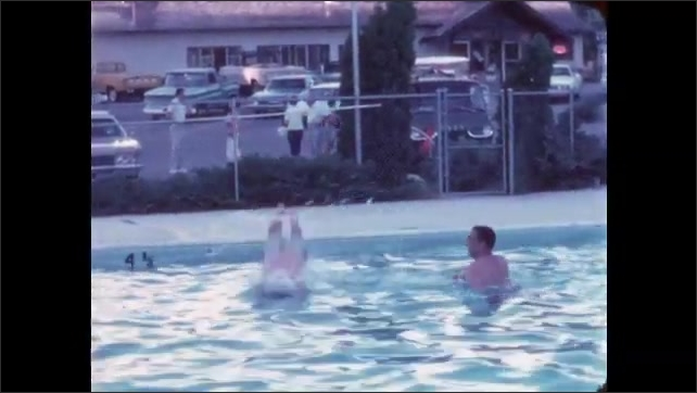 1960s: Woman sits in poolside chair, drinking a beverage, a dog runs behind her. Man in polka dot trunks side steps along pool, dives in and swims to camera, smiles.