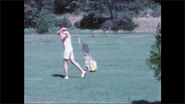 1960s: Golf course. Silver-haired man in khaki shorts putts, misses the hole, then taps it in. Slow-motion of woman in white shorts swinging and hitting ball.