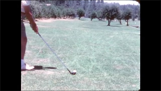 1960s: Golf course. Woman's feet as golf club hits ball towards hole. Man's legs in slacks and putter knocks ball into hole. Slow motion as man in khaki shorts swings and hits ball.
