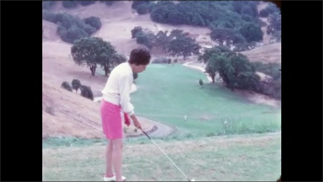 1960s: Golf course. Woman in pink shorts on hillside swings and hits ball up hill. On top off hill, lady swings and hits the ball into the valley. Man in khaki shorts places ball on tee.