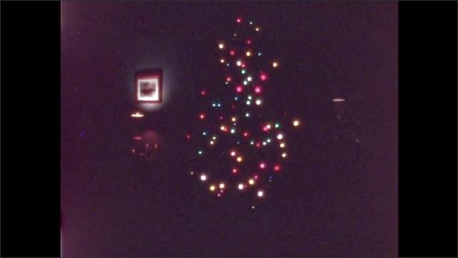 1950s: UNITED STATES: Christmas tree in corner of room. Lights on tree. Tree in darkness. Bulbs on tree.