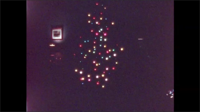 1950s: UNITED STATES: bulbs on Christmas tree in dark. Lights flash on and off