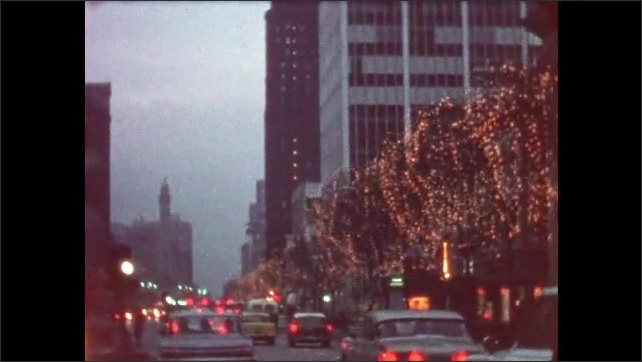 1950s: UNITED STATES: lights on trees in city at night. View along road through traffic
