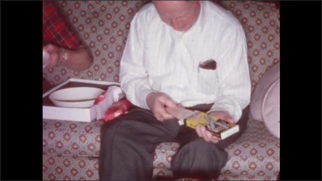 1950s: UNITED STATES: family members open up presents on Christmas day.
