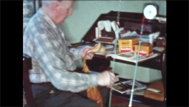 1950s: Man removes fishing pole from shiny wrapping. Man assembles fishing pole.