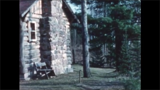 1950s: Cabins in woods. View of dock and lake.