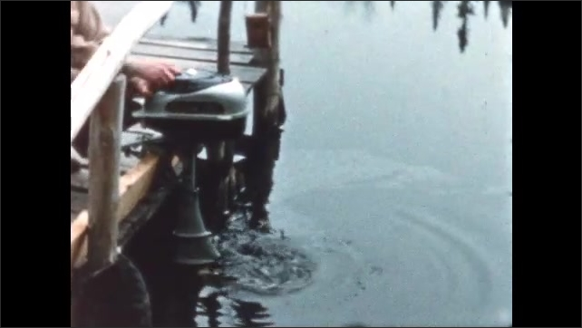 1950s: Man pulls starter cord on boat motor. Man stands by bush as woman walks by and into cabin.