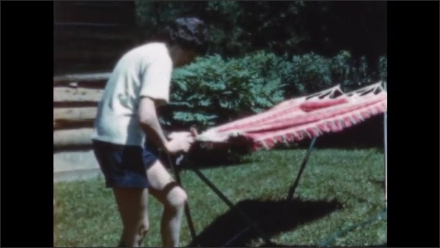 1950s: Woman attaches hammock to frame.