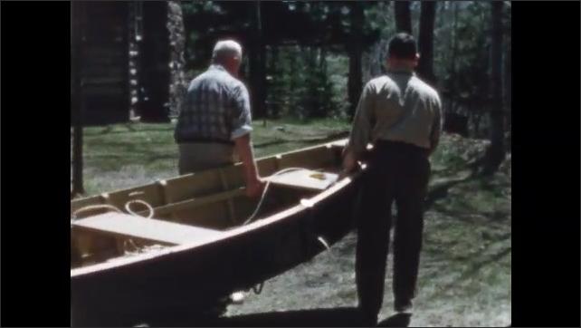 1950s: Men carry boat out of garage. Men wheel boat across yard.