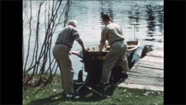 1950s: Men launch boat into water. Man waves while crouched on dock.