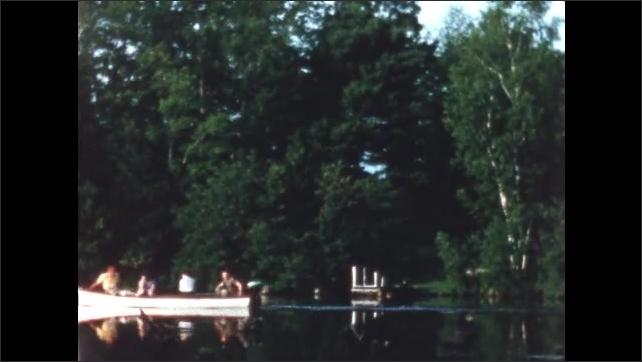1950s: Bridge over lake. People ride in boat. Man navigates boat.