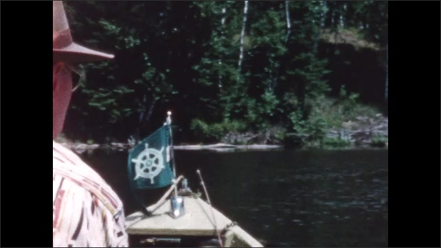 1960s: BRITISH COLUMBIA: CANADA: boat approaches shore and cabin on lake. Flag on front of boat.