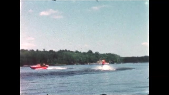 1960s: BRITISH COLUMBIA: CANADA: man water skis behind boat on lake. Motor boat and man on skis. Lady watches from jetty