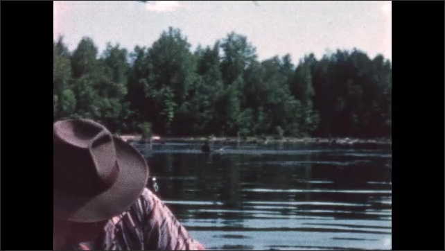 1960s: BRITISH COLUMBIA: CANADA: man sits on motor boat on lake. Man in sunhat and sunglasses on boat. Trees in lake.