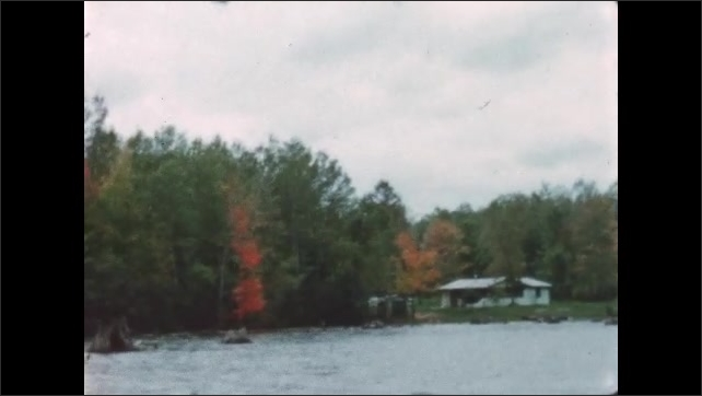 1960s: BRITISH COLUMBIA: CANADA: Autumn leaves by lake. Man on boat in Autumn. View towards leaves and changing colours