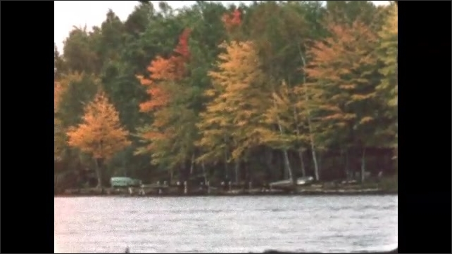 1960s: BRITISH COLUMBIA: CANADA: orange and yellow leaves on trees in Autumn. Cabin by lake