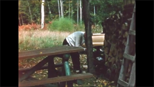 1960s: BRITISH COLUMBIA: CANADA: red and orange trees by lake. Leaves change colour on trees. Man saws wood into logs. Man saws logs by cabin