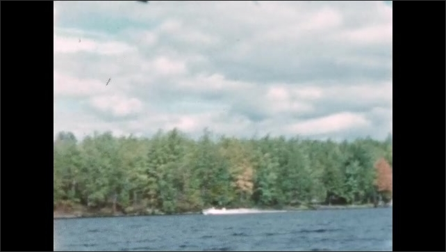 1960s: BRITISH COLUMBIA: CANADA: blue sky and clouds. Motor boat on lake. Trees by shore. Changing colours of leaves by lake