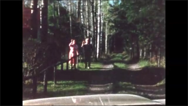 1960s: BRITISH COLUMBIA: CANADA: man waves at friends. Visitors leave cabin in woods. View along track to cabin