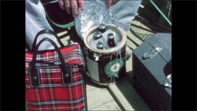 1960s: BRITISH COLUMBIA: CANADA: man sets up fishing gear in boat. Beer in cooler on boat. Man shows beer to camera.