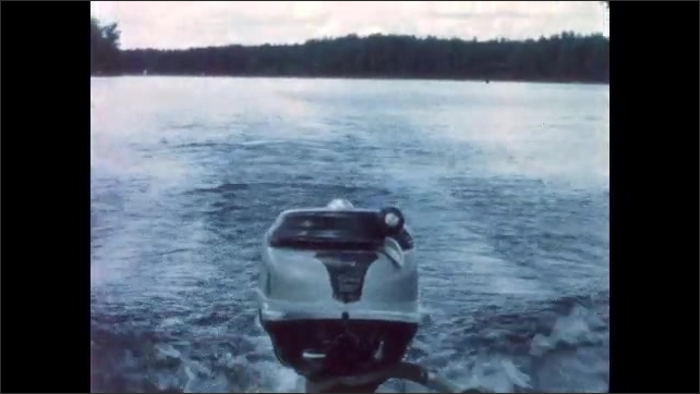 1960s: BRITISH COLUMBIA: CANADA: man enjoys view from boat. Motor on boat. Wake behind boat.