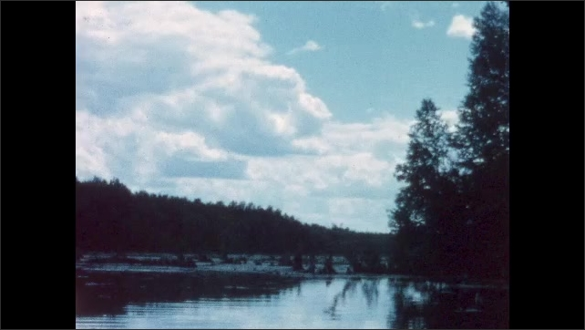 1960s: BRITISH COLUMBIA: CANADA: view of trees and shore from boat. Flooded trees and debris. Clouds over lake