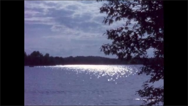 1960s: BRITISH COLUMBIA: CANADA: sunlight reflects on lake water. Clouds over lake.