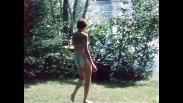 1960s: BRITISH COLUMBIA: CANADA: lady in bikini walks to shore of lake