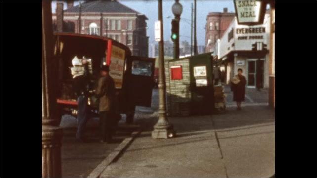 1960s: UNITED STATES: paintings in shop window. Man unloads van by sidewalk. Man carries goods to shop. Pedestrian in street.