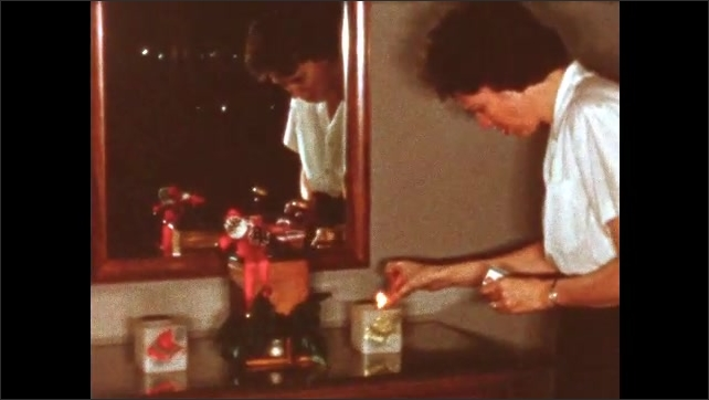 1960s: Woman in white shirt walks over to dresser topped with Christmas decorations with pack of matches, lights candles inside two milk glass cube candle holders, blows out match, walks away.