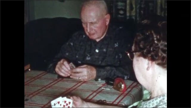 1960s: Three men and a woman sit around a table playing cards. They take turns throwing cards on the table, highest card takes the pile. Woman holds cards, put hand to face, reaches out.