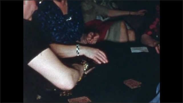 1960s: Woman in red dress gestures to cards on a table, 2 women talk behind her. Women sit around table playing cards. Woman in black deals, elderly woman in blue takes the first stack.