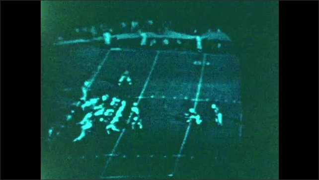 """1960s: Clips from the 1960 Pasadena Rose Bowl football game on a black and white TV. Kick-off. Three unsuccessful plays. Touchdown. Marching band forms """"1960"""" on the field."""
