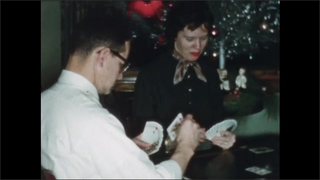 1960s: Men and women sit around table holding cards. Younger woman places card in middle. Younger man chooses, throws down card, followed by older man, woman scoops up the pile.