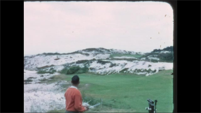 1960s: Golf course, sandy dunes, man takes practice swing, hits ball, places golf club back in rolling bag. Man walks down steep hill through sparse pine trees.