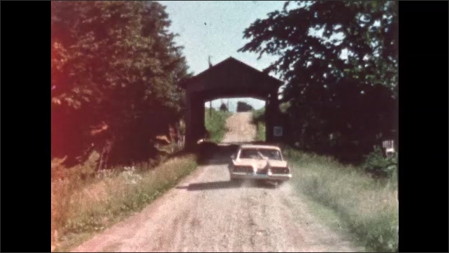 1960s: Car drives down dirt road, over small covered bridge.