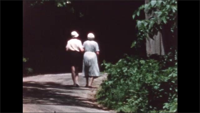1960s: Women walk arm in arm down road.