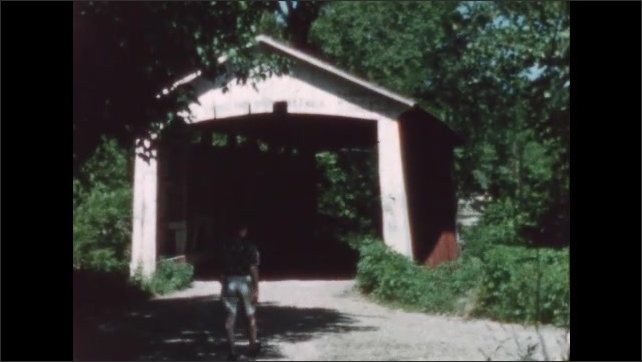 1960s: Car drives down dirt road, over small covered bridge. Man walks down dirt road, stands in front of covered bridge, waves, points up.