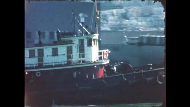 1960s: San Francisco piers. Small boat travels past larger boat anchored at pier.